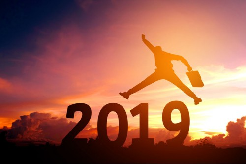 A person jumping over large block numbers spelling out 2019 with a sunset behind them