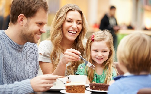 A man, woman, and young child laughing and eating pastries