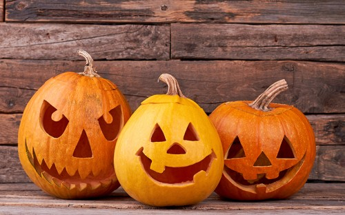 Three orange pumpkins with carved smiling faces against a wooden background