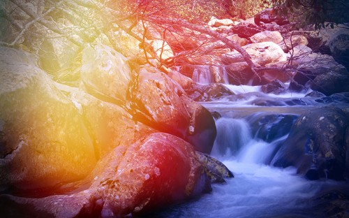 An illustration of water streaming down rocks with trees