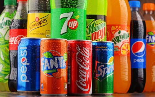 Multiple cans of colorful soda options in front of large bottles of soda